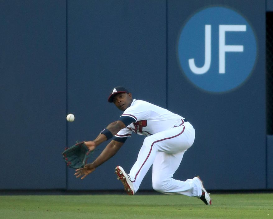 Atlanta Braves left fielder Justin Upton (8) catches the ball for an out on a hit by St. Louis Cardinals' Yadier Molina in the first inning of a baseball game, Wednesday May 7, 2014, in Atlanta. (AP Photo/Jason Getz)