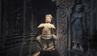 """FILE - This Wednesday, Dec. 18, 2013 file photo shows Cambodia's statue of a temple wrestler, titled Bhima, is on display at the Norton Simon Museum in Pasadena, Calif. The 10th-century sandstone statue will return to its place of origin in Cambodia following discussions and agreements with Cambodian state officials, the museum announced Tuesday, May 6, 2014. The statue represents Bhima, a popular heroic figure from the Hindu epic, """"The Mahabharata."""" The museum has carefully preserved it for nearly four decades, according to the release. The Bhima is considered a work of art and cultural relic for the Cambodian community. (AP Photo/Jae C. Hong, File)"""
