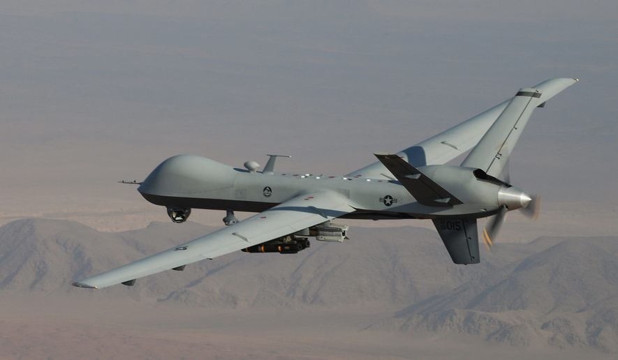 An MQ-9 Reaper patrols the skies with GBU-12 Paveway II laser guided munitions and AGM-114 Hellfire missiles. (U.S. Air Force) ** FILE **