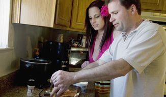 ADVANCE FOR USE SUNDAY, MAY 11 AND THEREAFTER - In this April 9, 2014 photo, multiple sclerosis patient Harold Johnson gets tips from his wife, Jessica, on putting together a pork chop dish at their home in Swansea, Ill. The experimental drug, Lemtrada, has kept his symptoms at bay since  2009. The drug has not yet been approved by the U.S. Food and Drug Administration, but is under review. (AP Photo/Belleville News-Democrat, Maureen Houston)