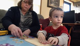 ADVANCE FOR USE SATURDAY, MAY 10 AND THEREAFTER - In this April 9, 2014 photo, three-year-old Caleb Coombs builds a puzzle with his mom, Lora, at their home near Lexington, Ill. Caleb is recovering from a rare brain tumor called anaplastic ependymoma. Systematically addressing challenges, whether it's solving a puzzle, re-coupling toy trains or improving in speech and physical therapy, is nothing new to Caleb. Once you've survived a rare brain cancer and treatment, puzzles, train wrecks and relearning how to swallow and walk in a straight line are all in a day's work. (AP Photo/The Pantagraph, David Proeber)