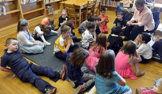 This March 21, 2014 photo, Sr. Sylvia Leonardi of the School Sisters of St. Francis sits with first graders in the library of St. Joseph Catholic Academy's Lower Campus in Kenosha, Wis.  Leonardi, who is a member of the School Sisters of St. Francis, has found great success with meditation exercises as a gateway to prayer. She is the campus minister and leader for enrichment intervention at the academy. (AP Photo/Kenosha News, Brian Passino)