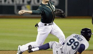 Oakland Athletics shortstop Jed Lowrie, top, turns a double play over Seattle Mariners' James Jones (99) on a ground ball from Robinson Cano during the fifth inning of a baseball game on Tuesday, May 6, 2014, in Oakland, Calif. (AP Photo/Marcio Jose Sanchez)