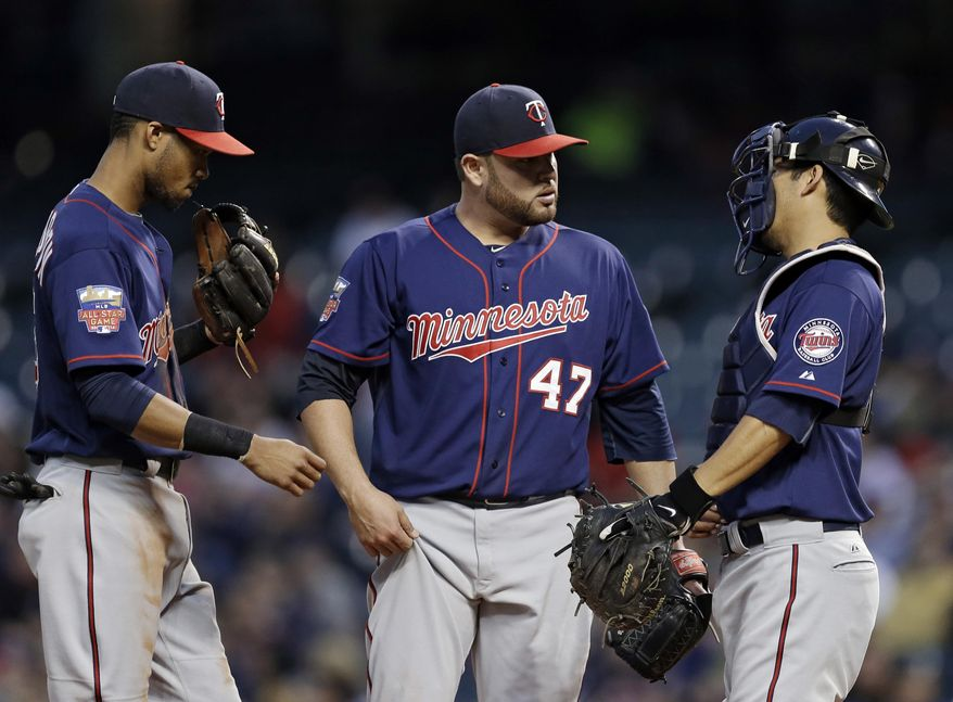 Minnesota Twins starting pitcher Ricky Nolasco (47) gets a visit from shortstop Pedro Florimon, left, and catcher Kurt Suzuki in the fifth inning of a baseball game against the Cleveland Indians Wednesday, May 7, 2014, in Cleveland. (AP Photo/Mark Duncan)