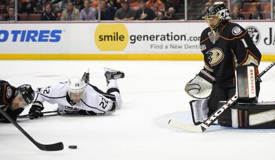Anaheim Ducks defenseman Mark Fistric, left, and Los Angeles Kings center Trevor Lewis, center, battle for the puck in front of goalie Jonas Hiller, of Switzerland, during the first period in Game 2 of an NHL hockey second-round Stanley Cup playoff series, Monday, May 5, 2014, in Anaheim, Calif.  (AP Photo/Mark J. Terrill)