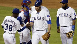 Texas Rangers manager Ron Washington (38) takes the ball from starting pitcher Colby Lewis as catcher Robinson Chirinos, second from left, Adrian Beltre, rear, and Elvis Andrus stand on the mound in the fourth inning of a baseball game against the Colorado Rockies, Wednesday, May 7, 2014, in Arlington, Texas. (AP Photo/Tony Gutierrez)
