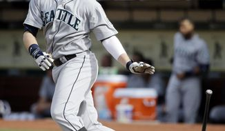 Seattle Mariners' Justin Smoak drops his bat as he singles during the fourth inning of a baseball game against the Oakland Athletics on Wednesday, May 7, 2014, in Oakland, Calif. (AP Photo/Marcio Jose Sanchez)