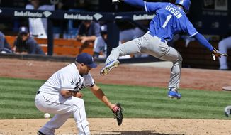 Kansas City Royals' Jarrod Dyson sails through the air while scoring over San Diego Padres pitcher Hector Ambriz after a passed ball during the eighth inning of a baseball game Wednesday, May 7, 2014, in San Diego.  (AP Photo/Lenny Ignelzi)