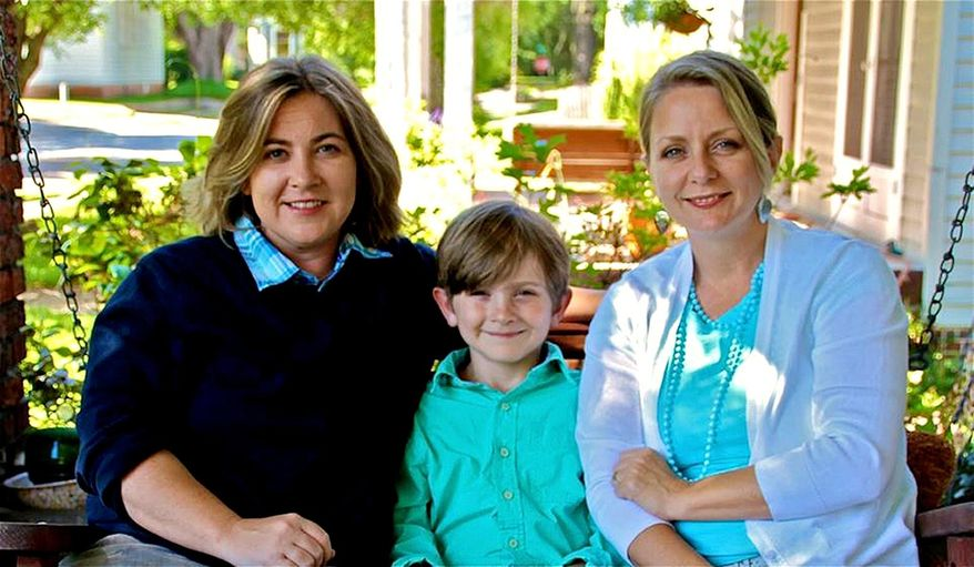 This undated photo provided by Cari Searcy, Searcy sits with partner Kimberly McKean, right, and their 8-year-old son Khaya at their home in Mobile, Ala. Searcy and McKean filed a federal lawsuit Wednesday seeking to force the state to recognize their out-of-state marriage so they can both be legal parents to their 8-year-old son. The suit contends that Alabama's ban on same-sex marriage and refusal to recognize such marriages from other states violates the equal protection clause of the U.S. Constitution. (AP Photo/Courtesy of Cari Searcy)