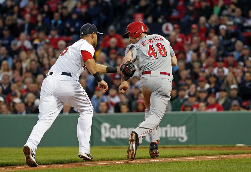 Cincinnati Reds' Ryan Ludwick (48) is tagged out by Boston Red Sox third baseman Will Middlebrooks during a rundown between third and home in the second inning of a baseball game at Fenway Park in Boston, Tuesday, May 6, 2014. (AP Photo/Elise Amendola)
