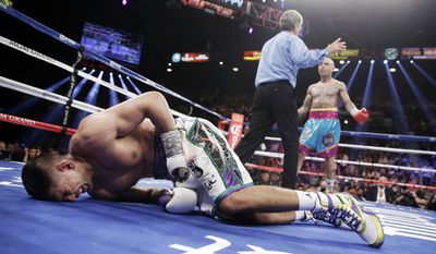 10ThingstoSeeSports - England's Amir Khan, left, crumbles to the mat after receiving a low blow from Luis Collazo, right, in their silver welterweight title boxing fight Saturday, May 3, 2014, in Las Vegas. Referee Vic Drakulich is at center. Khan went on to win by unanimous decision. (AP Photo/Isaac Brekken, File)