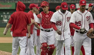 Washington Nationals catcher Wilson Ramos, center, is congratulated by teammate Bryce Harper, left, on the field after their win against the Los Angeles Dodgers in baseball game, Wednesday, May 7, 2014 in Washington. Nationals won 3-2.(AP Photo/Pablo Martinez Monsivais)
