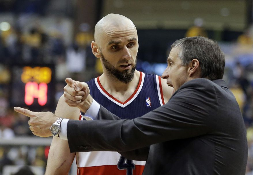 Washington Wizards head coach Randy Wittman talks with Marcin Gortat, left, during the first half of game 2 of the Eastern Conference semifinal NBA basketball playoff series against the Indiana Pacers, Wednesday, May 7, 2014, in Indianapolis. (AP Photo/Darron Cummings)