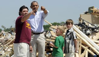 President Barack Obama tours tornado-damaged areas of Vilonia, Ark., Wednesday, May 7, 2014 and talks with Daniel Smith and his sons Garrison Dority and Gabriel Dority, right. Obama is visiting with first responders and families affected by the recent tornados before traveling on to California where he will raise money for the Democratic Party and receive an award from a foundation created by movie director Steven Spielberg. (AP Photo/Susan Walsh)