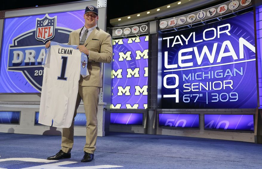 Michigan outside tackle Taylor Lewan poses for photos after being selected by the Tennessee Titans as the eleventh pick in the the first round of the 2014 NFL Draft, Thursday, May 8, 2014, in New York. (AP Photo/Craig Ruttle)