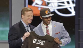 Oklahoma State cornerback Justin Gilbert, right, poses with NFL commissioner Roger Goodell after being selected by the Cleveland Browns as the eighth pick in the first round of the 2014 NFL Draft, Thursday, May 8, 2014, in New York.  (AP Photo/Frank Franklin II)