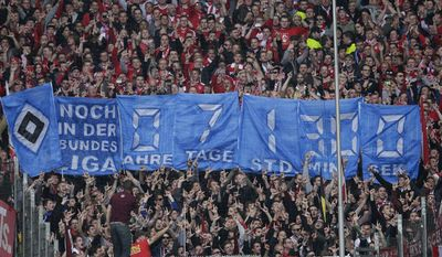 """Supporters of Munich display posters showing the """"remaining time"""" for the Hamburger SV being a member of the Bundesliga during the German Bundesliga soccer match between Hamburger SV and FC Bayern Munich in Hamburg, Germany, Saturday, May 3, 2014. (AP Photo/Michael Sohn)"""