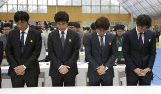 South Korea's national soccer team coach Hong Myung-bo, right, and other coaches pay silent tribute to the victims of the sunken ferry Sewol before announcement of the national team lineup for the upcoming Brazil World Cup at National Football Center in Paju, South Korea, Thursday, May 8, 2014. (AP Photo/Lee Jin-man)