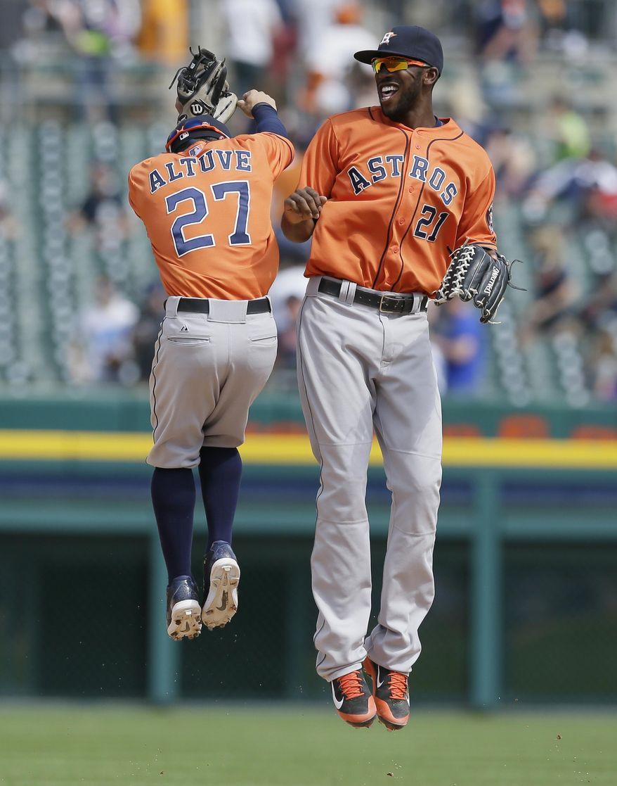 Houston Astros second baseman Jose Altuve (27) and center fielder Dexter Fowler celebrate their 6-2 win over the Detroit Tigers in a baseball game in Detroit, Thursday, May 8, 2014. (AP Photo/Carlos Osorio)