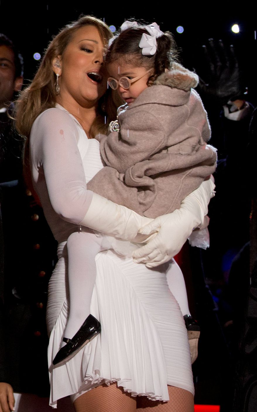 Singer and songwriter Mariah Carey holds her daughter Monroe Cannon on stage during the 2013 National Christmas Tree Lighting ceremony at the Ellipse in Washington, Friday, Dec. 6, 2013. (AP Photo/Carolyn Kaster)