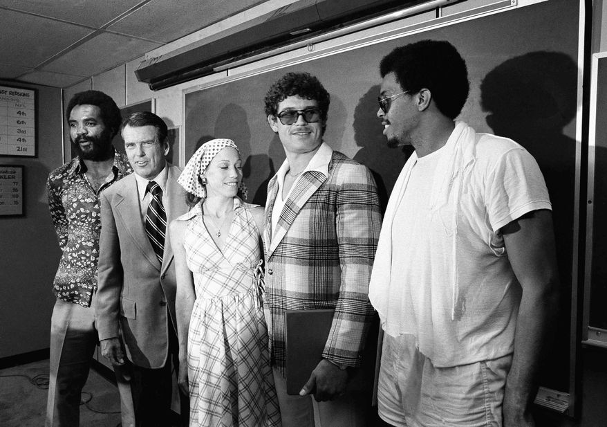 Washington Redskin head coach George Allen stands with two of his newly acquired running backs during a press conference at Redskins Park in Chantilly, Va., on Thursday, June 11, 1976.    From left are: Calvin Hill; Allen; Mrs. Mary Riggins; and John Riggins.  Mary Riggins is the wife of player Riggins.   (AP Photo/ Charles Harrity)