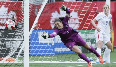 As USA's midfielder Heather O'Reilly (9) looks on goalkeeper Hope Solo (1) can't stop the header from Canada's defender Kadeisha Buchanan (20) during first half soccer action of a friendly match in Winnipeg, Manitoba, Thursday, May 8, 2014. (AP Photo/The Canadian Press, John Woods)