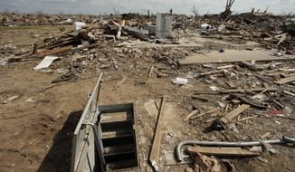 FILE - In this May 26, 2013, file photo, an underground shelter is seen near tornado rubble in Moore, Okla. The deadly tornadoes that killed more than 30 people scared Oklahomans in a way that previous storms had not, moving them to add tornado shelters or reinforced safe rooms to their homes. But the surge of interest in tornado safety has overwhelmed companies that build the shelters. Now there are long waiting lists, and many people have to endure the most dangerous part of the season with no added protection. (AP Photo/Charlie Riedel, File)