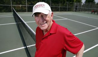 Marty Dowd, tennis coach for Catholic University of America, poses for a photograph, Thursday, May 8, 2014, in Washington. The 77-year-old coach led the Cardinals to the Landmark Conference title and a first-round match Friday against Washington & Lee in the NCAA Division III tennis tournament. (AP Photo/Alex Brandon)
