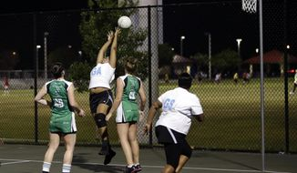 In this photo taken on Monday, April 28, 2014, April Blake, center, tries to stop the ball from going out of bounds during a netball game against  Myerscough College of England, in Lauderhill, Fla. U.S. netball enthusiasts hope to boost the game's profile here beyond clubs founded by Caribbean, British and Australian expatriates longing for a bit of home. (AP Photo)