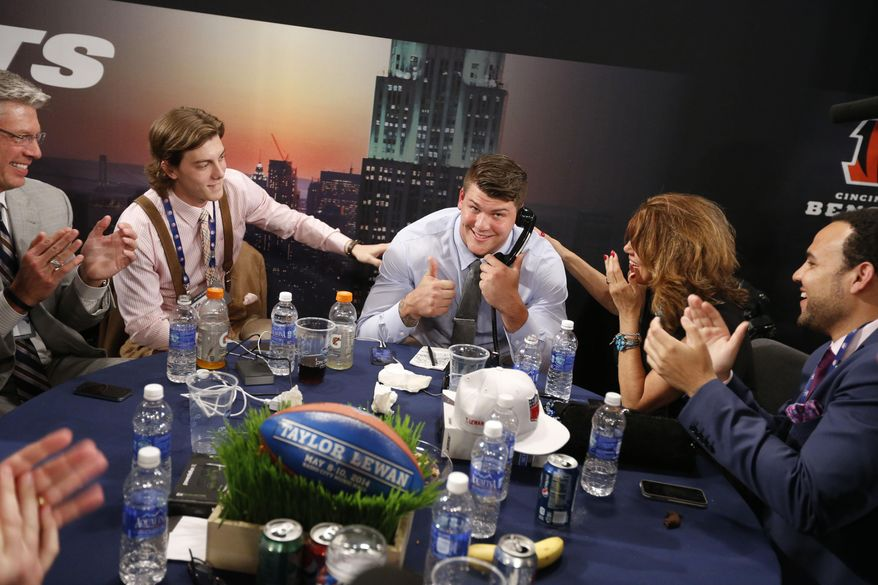 Taylor Lewan, from Michigan, reacts after being selected 11th overall by the Tennessee Titans in the first round of the NFL football draft, Thursday, May 8, 2014, at Radio City Music Hall in New York. (AP Photo/Jason DeCrow)