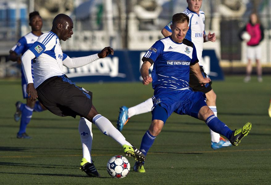 Montreal Impact's Hassoun Camara, left, controls the ball as Edmonton FC's Neil Hlavaty chases during first half action of the Amway Canadian Championship semi-final in Edmonton, Alberta, on Wednesday May 7, 2014.  (AP Photo/The Canadian Press, Jason Franson)