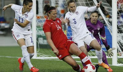 Canada's forward Melissa Tancredi (14) drives for the net as USA's goalkeeper Hope Solo (1) looks on as defenders Ali Krieger (11) and Christie Rampone (3) defend during the second half of an exhibition soccer match in Winnipeg, Manitoba, Thursday, May 8, 2014. (AP Photo/The Canadian Press, John Woods)