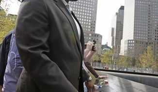 Cameroonian-born Cyrus Kouandjio, a defensive tackle from Alabama, looks at the north reflecting pool as he and members of the 2014 NFL Draft class  visit the 9/11 Memorial and Museum in New York, Wednesday, May 7, 2014.  (AP Photo/Kathy Willens)