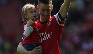 Arsenal's Laurent Koscielny, carrying his unidentified daughter, waves to the supporters as the team parade around the stadium in their last home match at the end of their English Premier League soccer match against West Bromwich Albion at Emirates Stadium in London, Sunday, May 4, 2014. (AP Photo/Sang Tan)