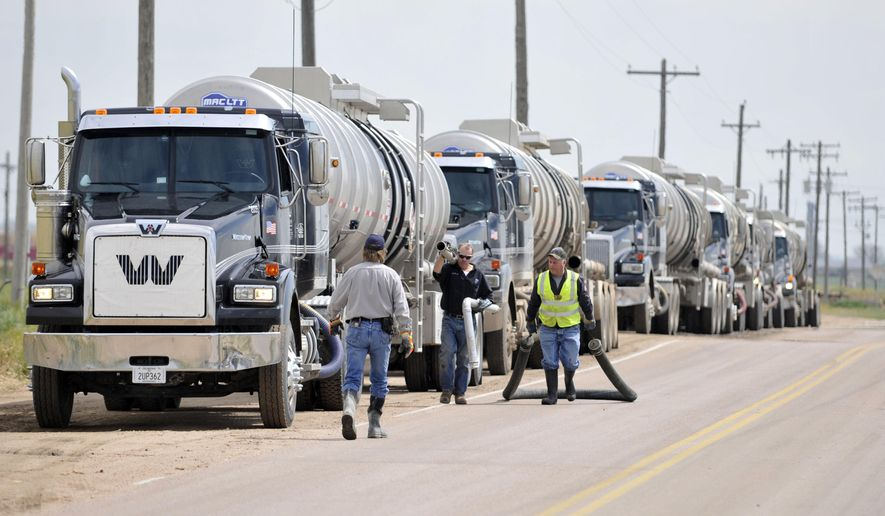 Oil tanker trucks line up along the Weld County Road 31 as they prepare to transfer oil after a train derailment southwest of LaSalle, Colo. on Friday, May 9, 2014. The train, loaded in Windsor with Niobrara crude bound for New York, derailed around 8 a.m. according to Union Pacific Spokesman Mark Davis. Officials found one car of the 100-car train was leaking. (AP Photo/The Greeley Tribune, Joshua Polson)