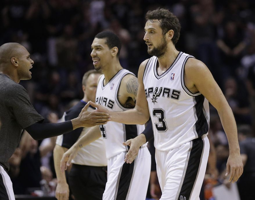 San Antonio Spurs' Marco Belinelli (3), of Italy, and Danny Green (4) are congratluted by teammate Patty Mills , left, as the walk off the court during the first half of Game 2 of a Western Conference semifinal NBA basketball playoff series against the Portland Trail Blazers, Thursday, May 8, 2014, in San Antonio.  (AP Photo/Eric Gay)