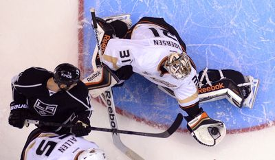 Anaheim Ducks goalie Frederik Andersen, right, of Denmark, makes a glove save as Los Angeles Kings left wing Kyle Clifford, upper left, and defenseman Bryan Allen look on during the first period in Game 3 of an NHL hockey second-round Stanley Cup playoff series, Thursday, May 8, 2014, in Los Angeles. (AP Photo/Mark J. Terrill)