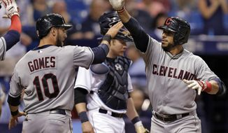 Cleveland Indians' Mike Aviles, right, greets Yan Gomes after hitting a three-run home run off Tampa Bay Rays relief pitcher Brandon Gomes during the seventh inning of a baseball game Friday, May 9, 2014, in St. Petersburg, Fla. Indians' Asdrubal Cabrera also scored on the hit. (AP Photo/Chris O'Meara)