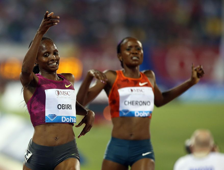 Hellen Obiri of Kenya, left, celebrates winning the women's 3000m at the IAAF Diamond League in the Qatari capital Doha, Friday May 9, 2014. (AP Photo/Osama Faisal)