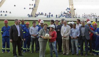 Brazil's President Dilma Rousseff, center poses for pictures with construction workers as she visits the Itaquerao stadium in Sao Paulo, Brazil, Thursday, May 8, 2014. The still unfinished stadium will host the World Cup opener match between Brazil and Croatia on June 12. (AP Photo/Andre Penner)