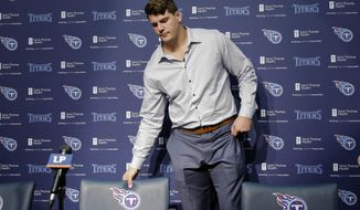Tennessee Titans first round draft pick Taylor Lewan, an offensive lineman from Michigan, takes his seat at an NFL football news conference Friday, May 9, 2014, in Nashville, Tenn. Lewan was the 11th overall pick in Thursday's NFL draft. (AP Photo/Mark Humphrey)