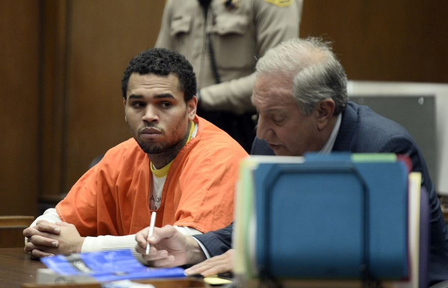 Chris Brown, left is shown in court with his attorney, Mark Geragos Friday May 9, 2014 in Los Angeles. Brown on Friday admitted a probation violation over an altercation last year outside a hotel in Washington, D.C., and was sentenced to remain on probation and serve an additional 131 days in jail. (AP Photo/Paul Buck, POOL)