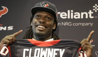 Jadeveon Clowney, the Houston Texans No. 1 overall draft pick, holds up his new jersey and jokes about where to look during an NFL football press conference Friday, May 9, 2014, in Houston. (AP Photo/Pat Sullivan)