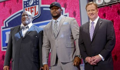 Minnesota defensive tackle Ra'Shede Hageman, center, poses for photos with NFL commissioner Roger Goodell, right, and former NFL player Claude Humphrey after being selected by the Atlanta Falcons as the 37th pick during the second round of the 2014 NFL Draft, Friday, May 9, 2014, in New York. (AP Photo/Jason DeCrow)