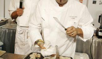 In a Aug. 3, 2008 file photo, Chef John Currence, front, of Mississippi,  is photographed during a cooking competition in New Orleans, La., Currence, an Oxford. Miss., restaurateur will join other Mississippi chefs June 13, when they and others will participate in the Big Gay Mississippi Welcome Table at City Grit, a private dinner club in New York. The dinner was organized to show opposition to the religious restoration act, and it's being held the night before the 35th annual Mississippi picnic in Central Park, where state promoters serve fried catfish and sweet tea. (AP Photo/The Times-Picayune, Eliot Kamenitz)