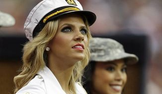 ADVANCE FOR WEEKEND EDITIONS, MAY 10-11 - FILE - In this Nov. 17, 2013, file photo, Houston Texans cheerleader Caitlyn watches from the sideline during the second half of an NFL football game against the Oakland Raiders in Houston. Mike Ramirez is a Texas high school football player who spent most of his time on the bench last season and works part-time at a local McDonalds. Caitlyn is a Texans cheerleader whose life is devoted to intense workouts, coaching tumbling classes and studying communications at the University of Houston. Yet 10,000 retweets later, the two are headed to the prom this Saturday on a blind date resulting from social media. (AP Photo/Patric Schneider, File)