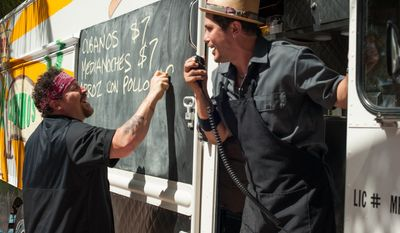 """This image released by Open Road Films shows Jon Favreau, left, and John Leguizamo in a scene from """"Chef."""" (AP Photo/Open Road Films, Merrick Morton)"""