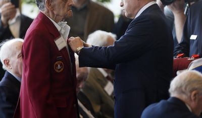 Guy Wildenstein, president of the American Society of the French Legion of Honor, right, presents an the legion's insignia to World War II veteran Emilio Vizachero Jr., during a ceremony at the U.S. Military Academy on Friday, May 9, 2014, in West Point, N.Y. Thirty-four U.S. veterans were honored 70 years after of the D-Day landings. (AP Photo/Mike Groll)