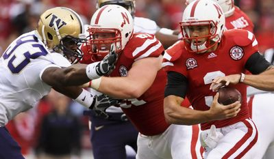 In this photo taken Sept. 17, 2011, Nebraska offensive lineman Spencer Long, second from left, holdsback Washington's Andrew Hudson (93) as Nebraska quarterback Taylor Martinez (3) carries the ball in the first half of an NCAA college football game in Lincoln, Neb. The Nebraska offensive line finally flexed its muscles after being criticized for not being able to push anyone around. (AP Photo/Dave Weaver)