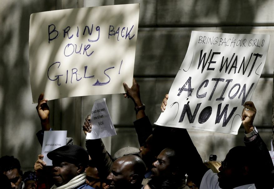 Demonstrators hold banners as they protest about the kidnapping of girls in Nigeria, near the Nigerian High Commission in London, Friday, May 9, 2014. Global outrage against the abduction of more than 200 Nigerian girls by Islamist militant sect Boko Haram heated up Thursday, as a social media campaign drew worldwide support. (AP Photo/Kirsty Wigglesworth)